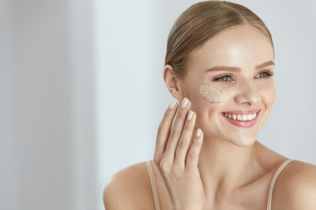 Face Skin Scrub. Smiling Female Applying Scrub On Face Skin