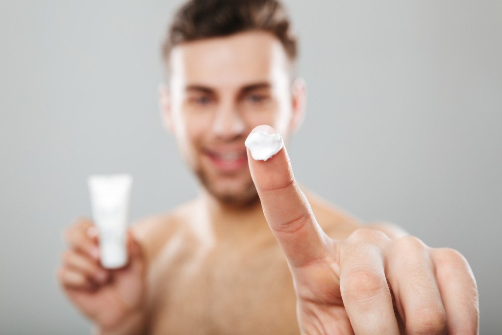 Beauty portrait of a half naked man applying face cream